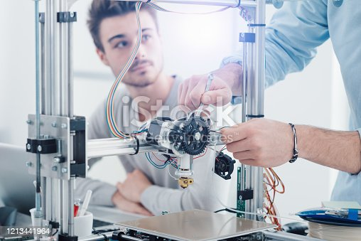 506677574 istock photo Young researchers and 3D printing 1213441964