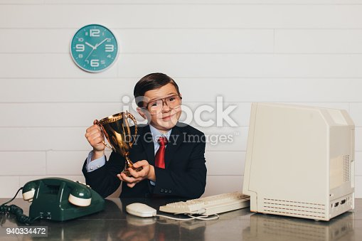 istock Young Retro Business Boy in Office with Trophy 940334472