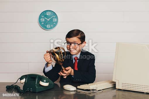 istock Young Retro Business Boy in Office with Trophy 940334474