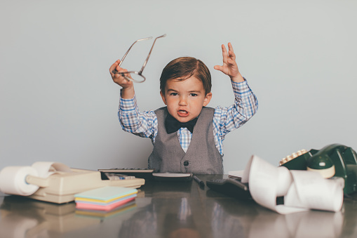 A little retro business boy dressed in bow tie, eyeglasses and vest answers the telephone at his business office desk. He is frustrated and angry at the chaotic situation at work and is overworked. He is holding up his eyeglasses in anger.