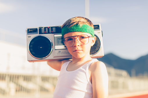 A young boy dressed in headband and retro workout attire is having a great time listening to music on his boombox. He has a serious expression on his face and is excited for health.
