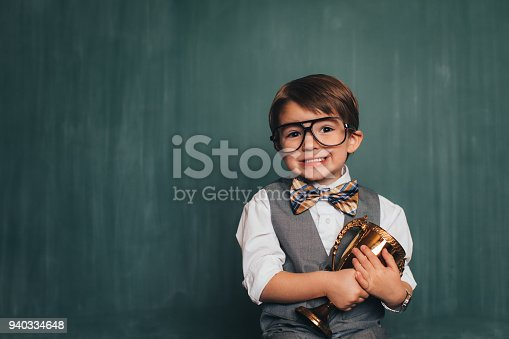 istock Young Retro Nerd Boy in Classroom with Trophy 940334648