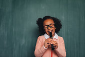 A young nerd girl dressed in sweater, eyeglasses plays her recorder. She has a fun smile on her face and is ready to become a master of music. Music is cool.
