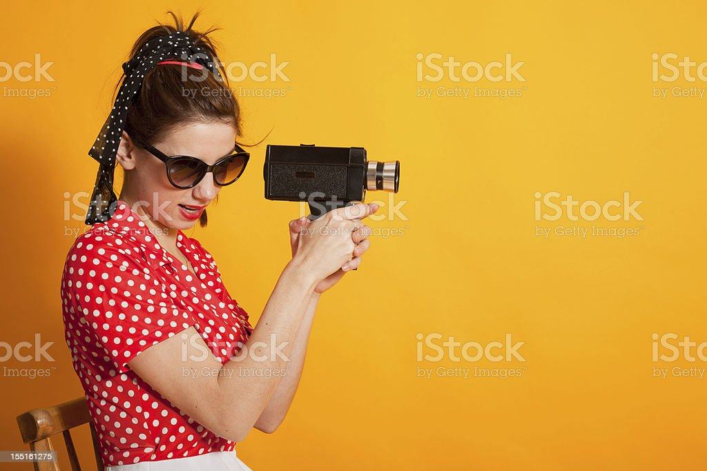 Young retro woman filming stock photo