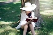 Young retro woman reading a book in the countryside