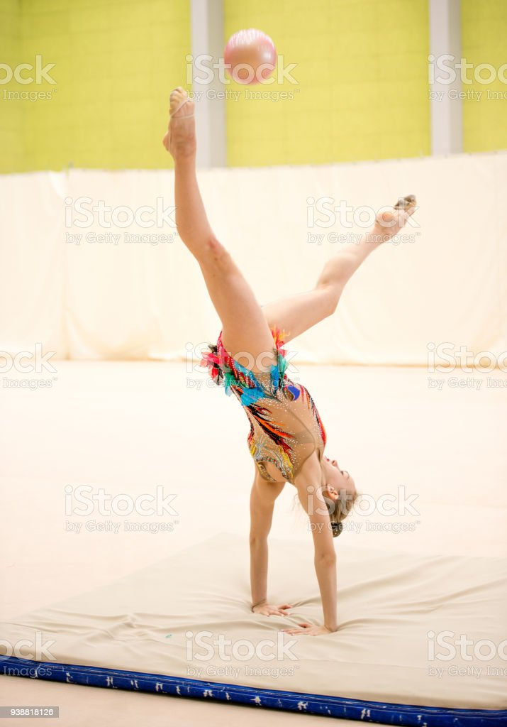 Young Rhythmic Gymnastics Athlete Catching the Ball with Legs in...
