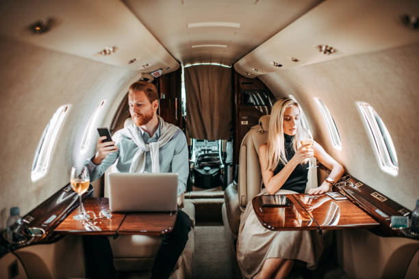 Young rich and successful couple looking away from each other while travelling in a private airplane Young rich, well-dressed couple traveling in a private jet, looking like they're having relationship difficulties. Man is using a mobile phone while a woman is drinking wine. status symbol stock pictures, royalty-free photos & images
