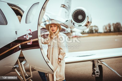 Young rich blonde female entering a private airplane parked on an airport tarmac. She is looking over her shoulder.