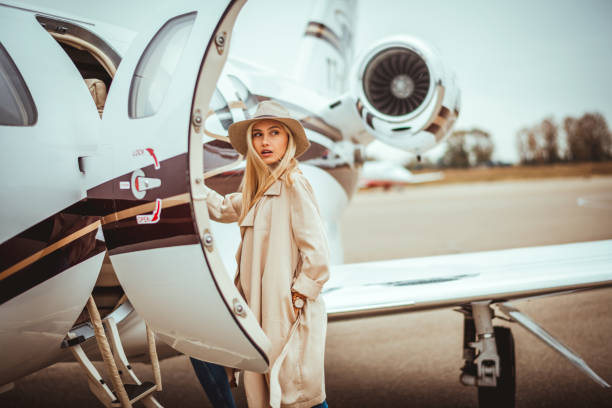 Young rich blonde female looking over her shoulder while entering a private airplane parked on an airport tarmac Young rich blonde female entering a private airplane parked on an airport tarmac. She is looking over her shoulder. first class stock pictures, royalty-free photos & images
