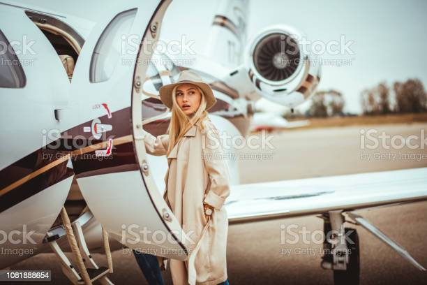 Photo of Young rich blonde female looking over her shoulder while entering a private airplane parked on an airport tarmac