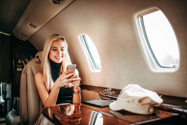Young rich blonde woman using a mobile phone while traveling on a private jet stock photo