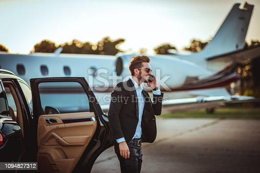 Young rich manager talking on a smart phone while getting out of a luxurious car parked next to a private airplane on a taxiway.