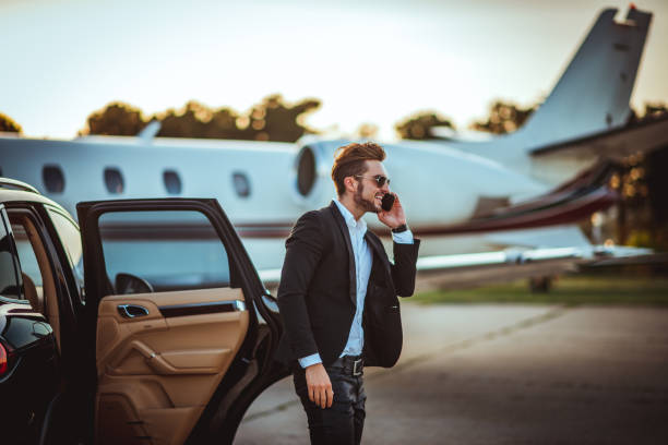 Young rich businessman talking on a mobile phone while getting out of a luxurious car parked next to a private airplane on a tarmac Young rich manager talking on a smart phone while getting out of a luxurious car parked next to a private airplane on a taxiway. high society stock pictures, royalty-free photos & images