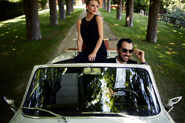 Young rich couple travel on the new white convertible Happy couple enjoying a ride on their luxury convertible in the summer,gorgeous rich woman feels so glad while they riding on cabriolet with sure handsome brunette man, romantic couple at journey trip high society stock pictures, royalty-free photos & images