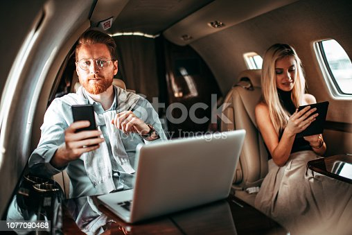 istock Young rich couple using smart phone and a digital tablet while travelling together aboard a private jet 1077090468
