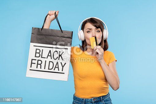 istock Young rich customer with credit card showing you paperbag 1166147957
