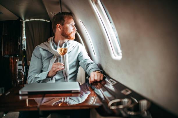 young rich man enjoying a glass of wine while sitting in a private jet - consumo exibicionista imagens e fotografias de stock