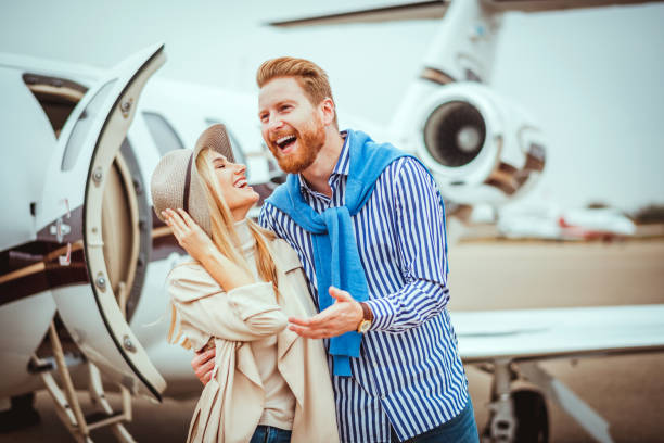 young rich man hugging his partner tight next to a private jet parked on an airport runway - consumo exibicionista imagens e fotografias de stock
