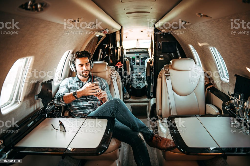 Young Rich Man Listening To Music Over The Headphones And Using A Mobile Phone While Sitting In ...