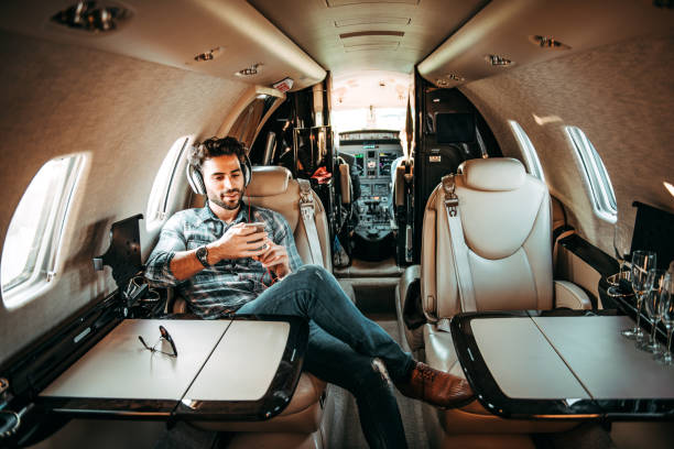 Young rich man listening to music over the headphones and using a mobile phone while sitting in a private jet Young successful man listening to music over the headphones while sitting in a private airplane. Sunglasses are on the table in front of him. status symbol stock pictures, royalty-free photos & images