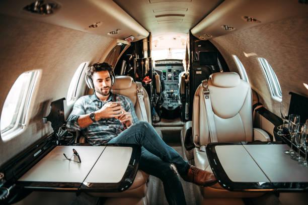 Junge reiche Mann Musik über die Kopfhörer hören und Benutzung eines Mobiltelefons während der Sitzung in einem privat-jet – Foto