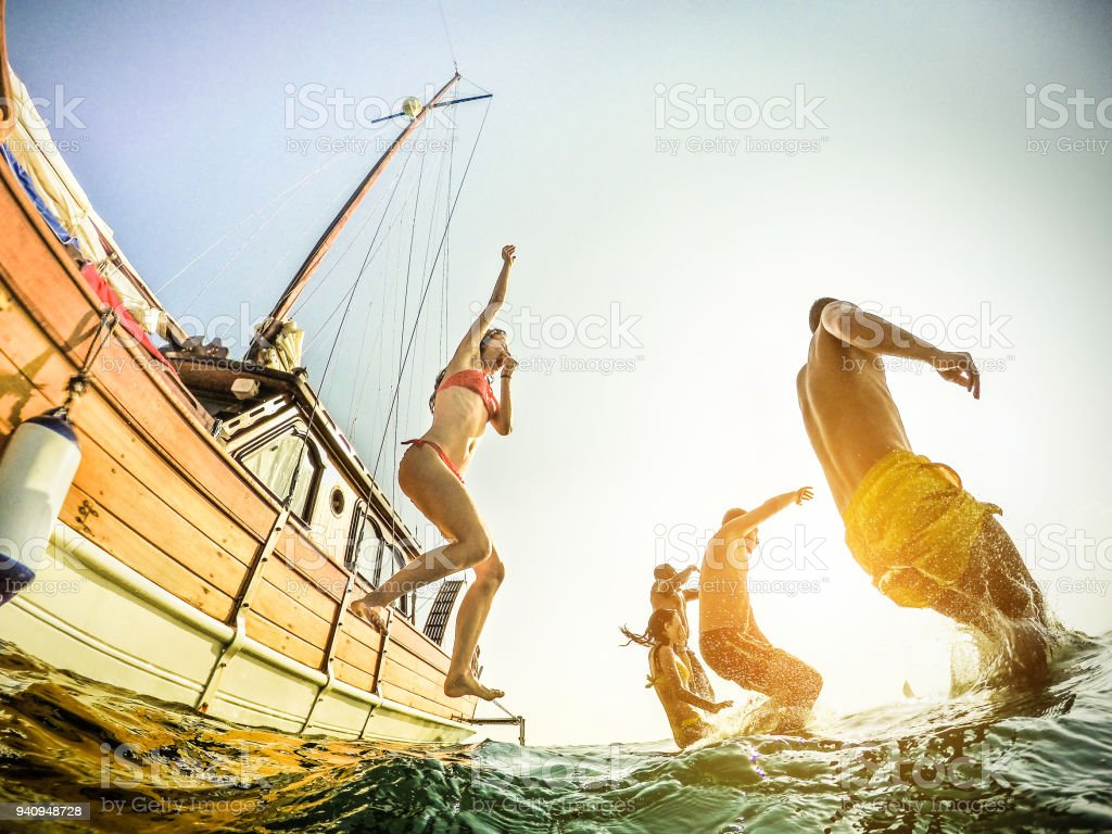 Young Rich People Diving From Sailing Boat Into The Sea