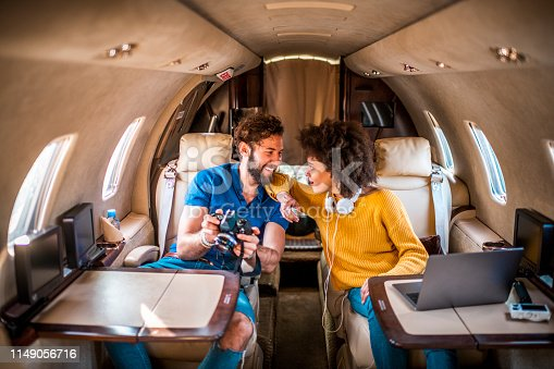 Rich and successful young tourist couple sitting inside a private airplane and looking at a DSLR camera.