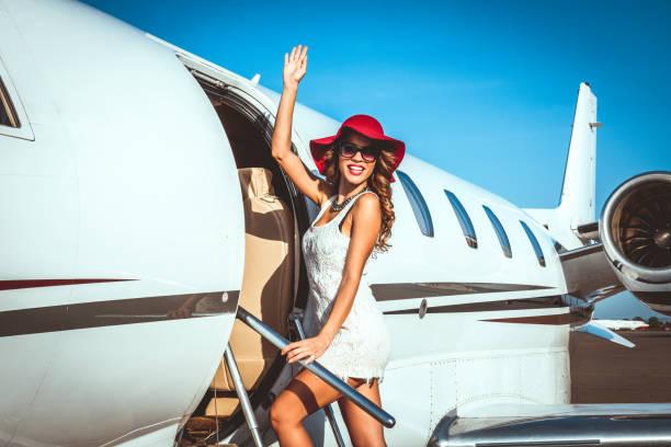 Junge reiche Frau in einen geparkten einem Privatflugzeug und winken beim Blick über die Schulter – Foto
