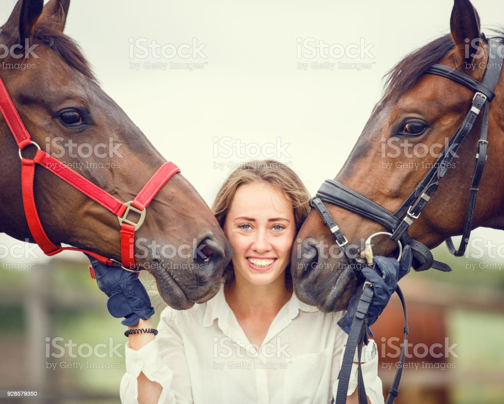 Young rider girl having fun with two her horses stock photo