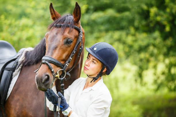 馬を保持しているヘルメットで若いライダー女性 - 乗馬 ストックフォトと画像