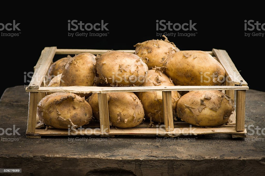 Young ripe potatoes in a wooden crate stock photo