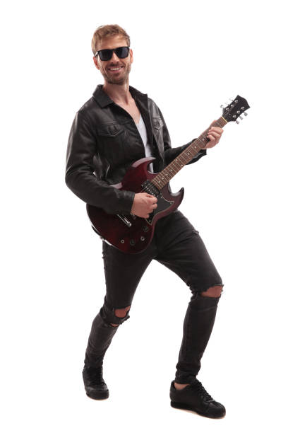 young rock star performing on guitar and smiling stock photo