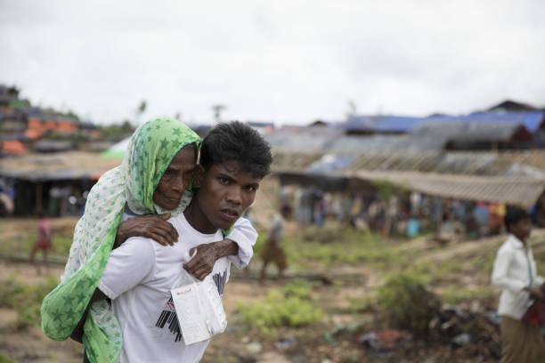Young Rohingya man carying senior Rohingya woman in refugee camp. Young Rohingya man carrying senior Rohingya woman in refugee camp. rohingya culture stock pictures, royalty-free photos & images