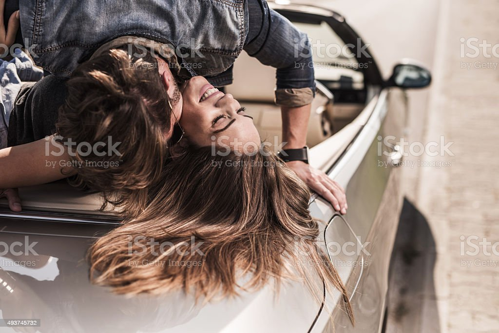 Young romantic couple enjoying in their love on a convertible. stock photo