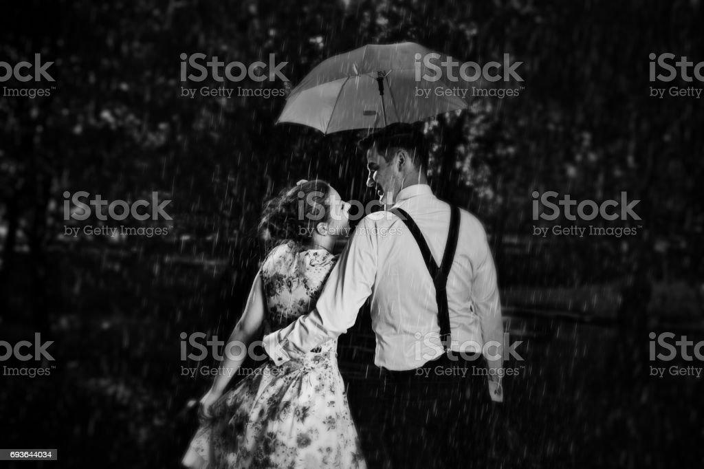 Jeune couple romantique amoureux flirter sous la pluie. Noir et blanc - Photo