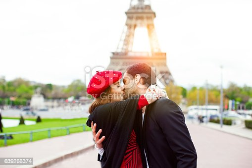 Young romantic couple kissing near the Eiffel Tower in Paris. Image taken during istockalypse Paris 2016