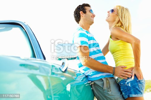Side view of young romantic couple leaning against convertible car
