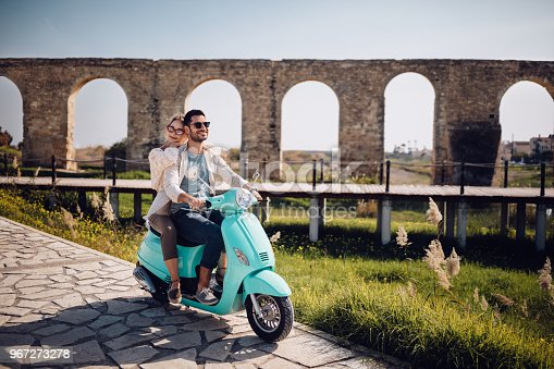 Young loving couple with vintage motorcycle riding next to ancient stone aqueduct monument in Spain