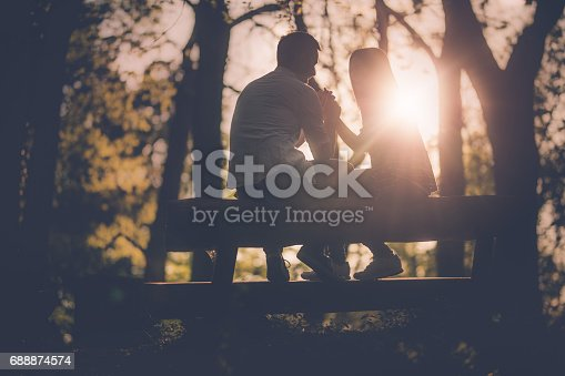 Happy couple relaxing on a bench in the forest while holding hands and communicating.