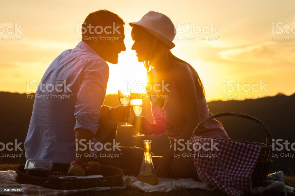Young romantic couple toasting with wine at sunset. stock photo
