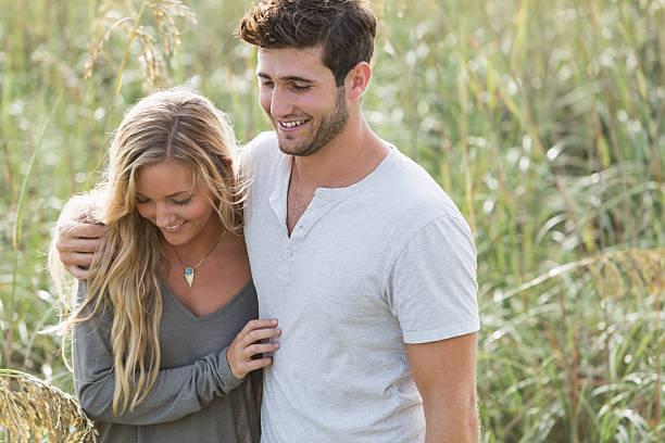 junge romantisches paar zu fuß am strand sand dunes - sanft und sorgfältig stock-fotos und bilder