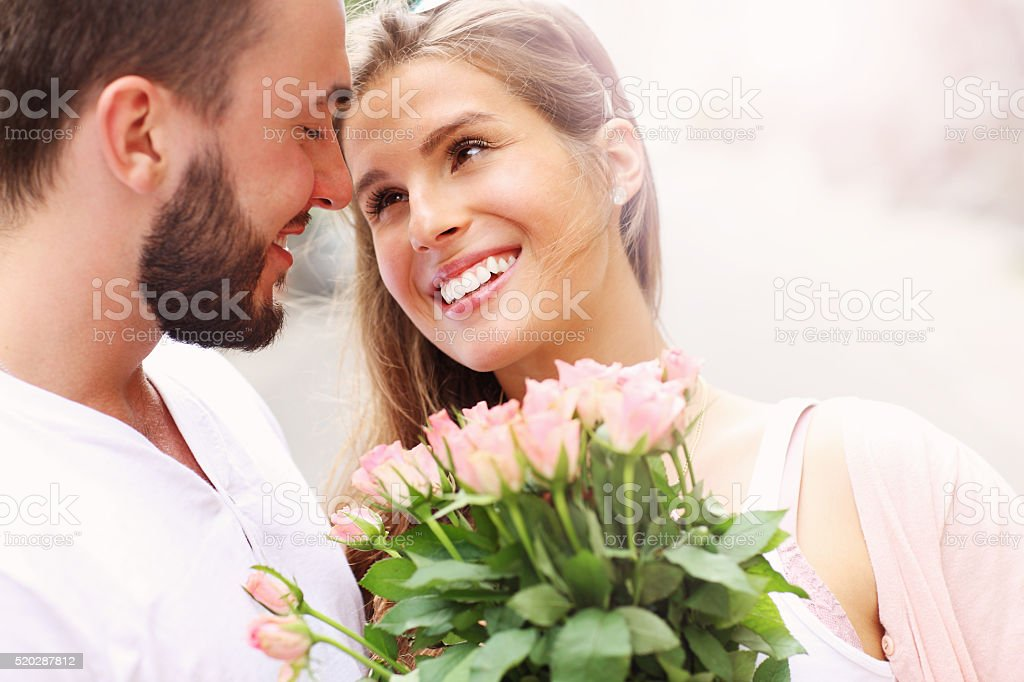 Young romantic couple with flowers stock photo