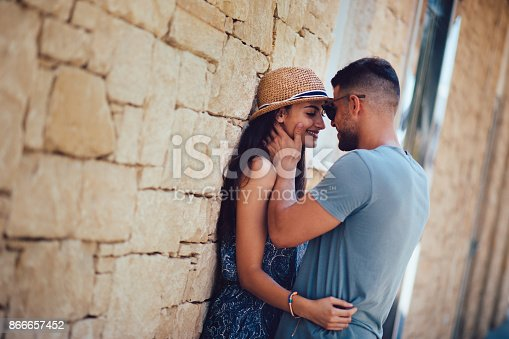 istock Young romantic hipster couple flirting against stone wall in summer 866657452