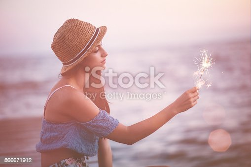 Young beautiful hipster woman with sparkler daydreaming sitting on wooden pier on summer holidays