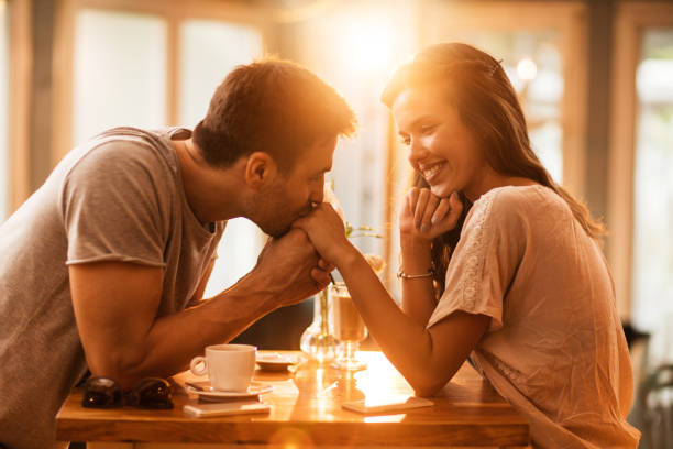 Young romantic man kissing girlfriend's hand in a cafe. Smiling woman enjoying in a cafe while being kissed in a hand by her boyfriend. romantic activity stock pictures, royalty-free photos & images