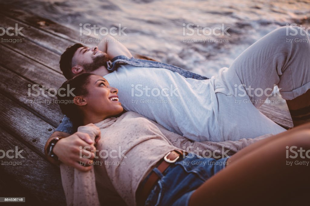 Young romantic multi-ethnic hipster couple lying down on jetty together stock photo