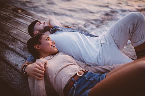 junge romantische multiethnischen hipster paar zusammen am steg liegend - schwarze romantik stock-fotos und bilder