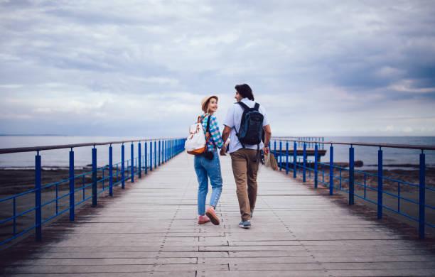 junge romantische reisende paar hand in hand und fuß am steg - hochzeitsreise zypern stock-fotos und bilder