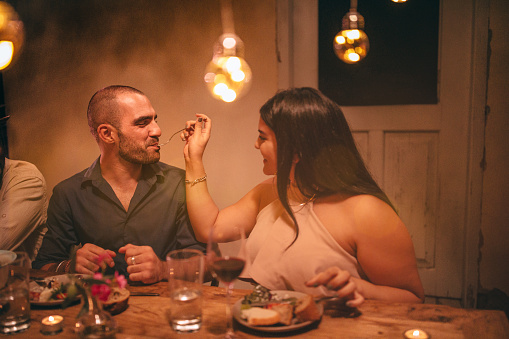 Happy smiling romantic couple eating at mediterranean rustic cottage dinner party