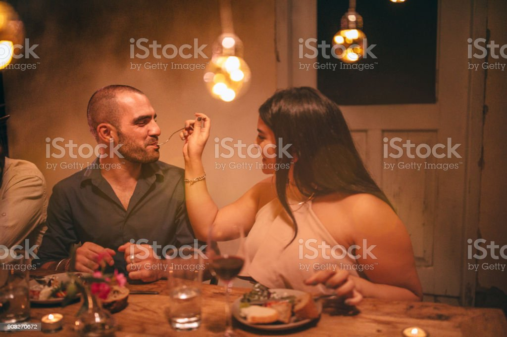 Young romantic woman feeding boyfriend at rustic dinner party stock photo